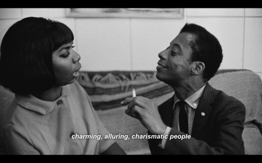 Nina Simone and James Baldwin seated on a couch facing each other, in conversation. James is holding the stub of a cigarette and smiling impishly at Nina.