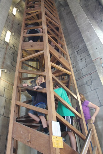 The author and her children climb a tight wooden spiral staircase