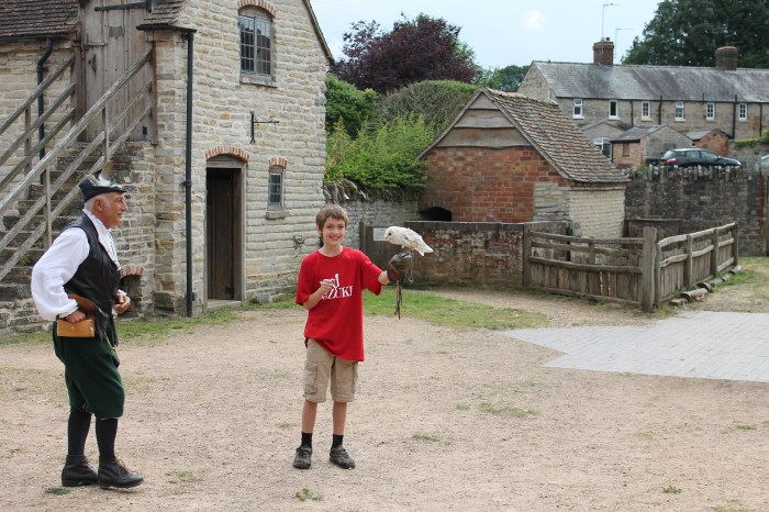 The author's son stands next to a costumed Falcon Master. The child is holding a white owl and grinning happily.
