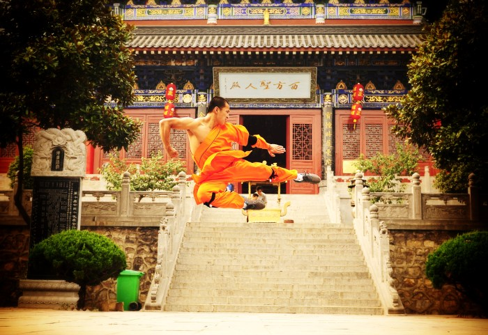 A shaolin monk is pictured flying through the air in an impressive wushu form.