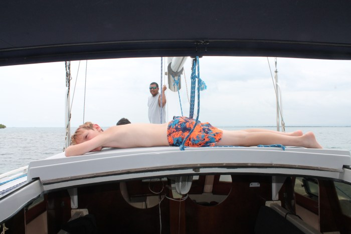 A boy lays on top of the roof of a catamaran