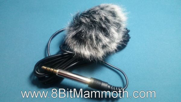A photo of a microphone with a wind muff attached