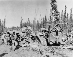 Black soldiers using logs for corduroy to free a D8 bulldozer stuck in the mud 1942.