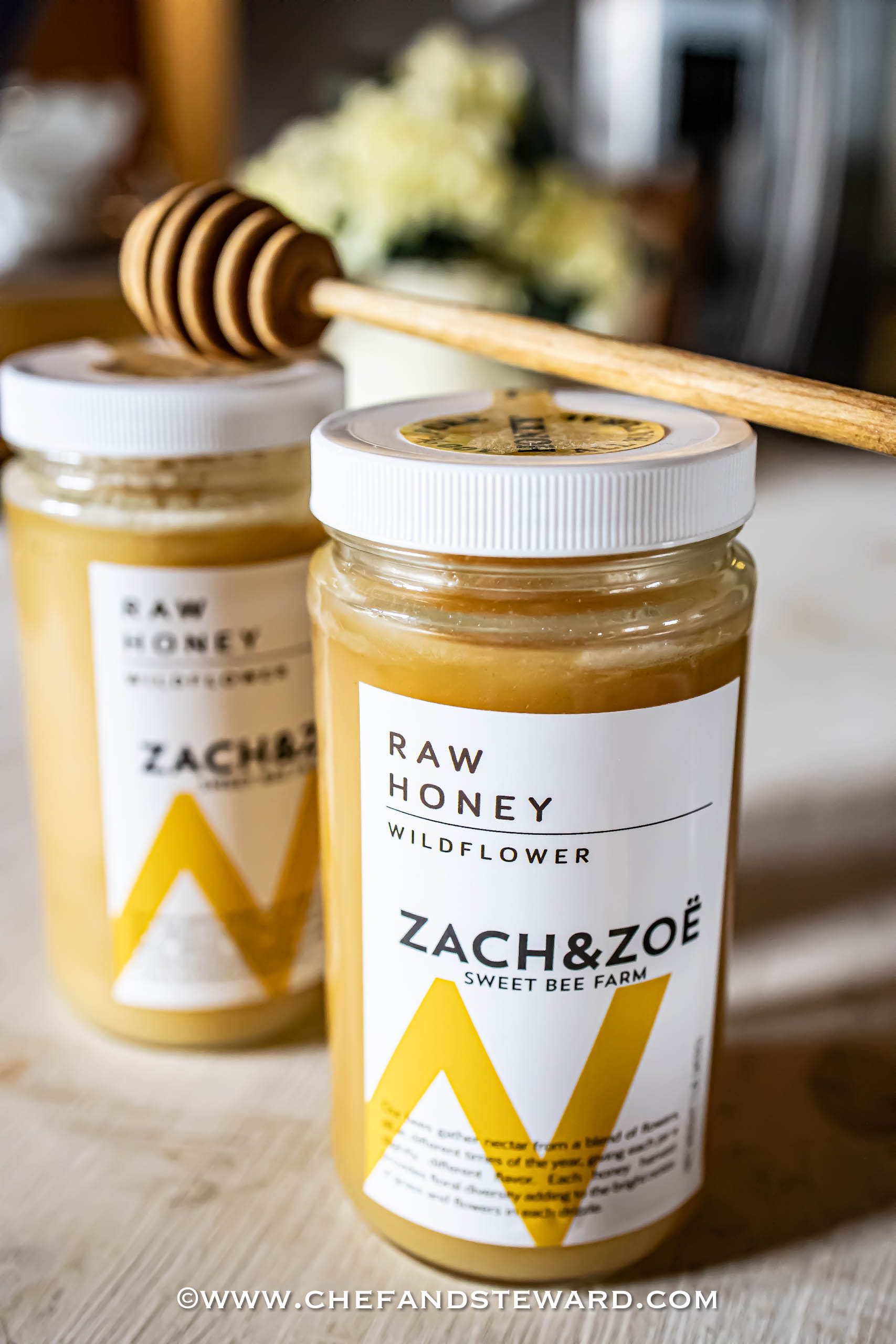Picture of two jars of Zach and Zoe honey with honey dipper and flowers in background