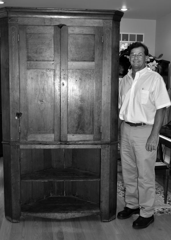 Haaff poses next to the cabinet, still beautiful but showing wear. Note the gnawed spot atop the upper doors. - - Photos by Kathy Tretter