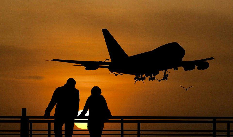 2 people watching a plane takeoff at sunset before heading oout on their own trip
