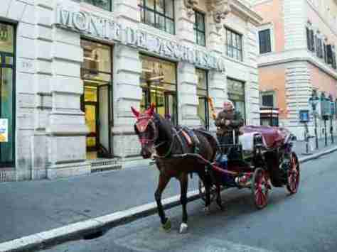A horse-drawn carriage passes a branch of Banca Monte dei Paschi bank in Rome.
