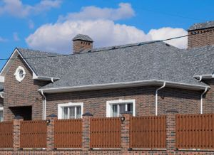 Asphalt shingle. Decorative bitumen shingles on the roof of a brick house. Fence made of corrugated metal.