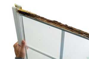 a person holding a rotten wooden window frame