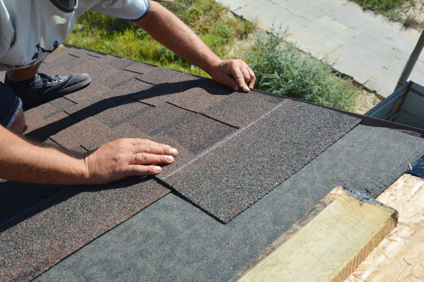 Roofer installing asphalt shingles on house construction roof corner. Roofing construction. Roofing contractor install roof tiles.