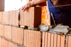Mason, bricklayer worker is using red blocks