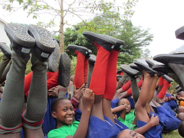 students raising feet in air