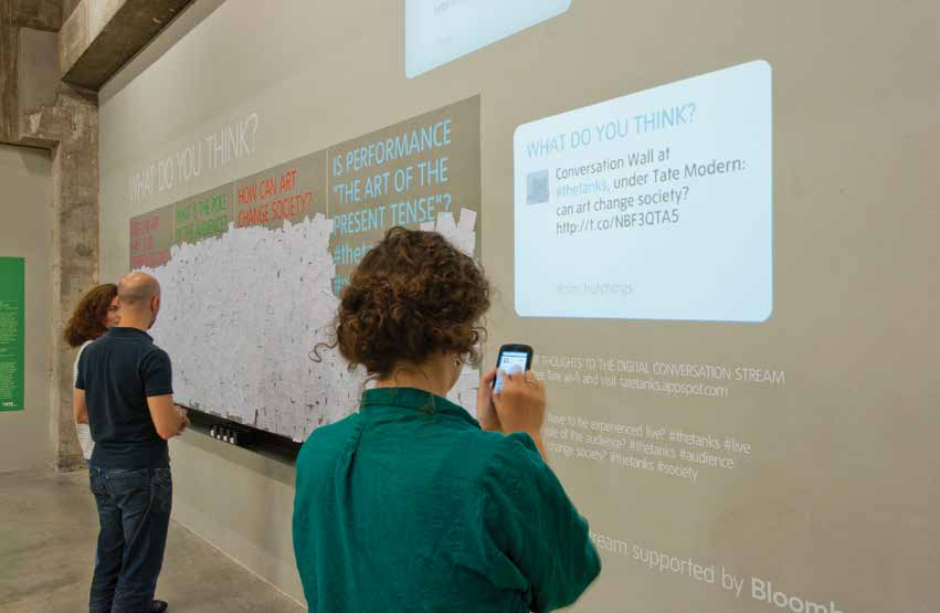 People standing in front of an interactive wall with their smart phones showing what they are tweeting about.