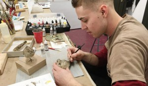 "Collin Moret, an assistant preparator, consults a field guide and ""study skin"" taxidermy mount while painting a sandpiper model."