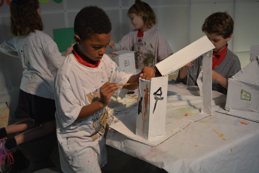 Four students build sculptures from cardboard.