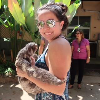 Gabriela smiling at the camera holding a real sloth
