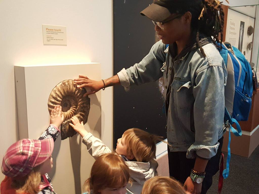 Several young children stand around a mollusk fossil with their hands outstreached. An adult shows them it is okay.