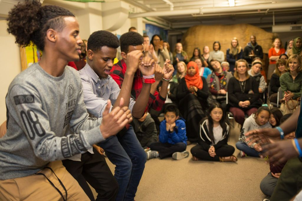A group of young men dance in front of a crowd of people