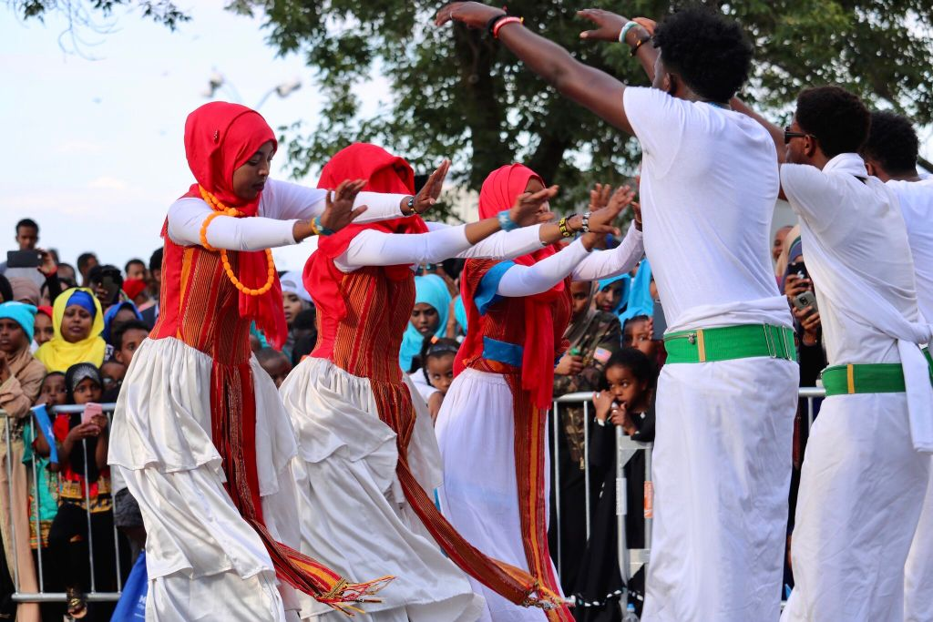 A group of women dressed in traditional Somali garb dance at a festival