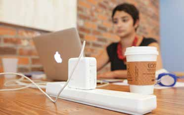 A woman sits with her computer and a cup of coffee in what looks like a coffeehouse. A man sits on a couch with his laptop in a place called the Cove.