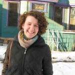 Woman stands in snow wearing heavy winter coat with scarf and short curly brown hair smiling, eyes squinted.