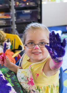 A little girl holds her hand up. It is covered in purple finger paint