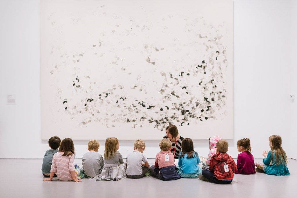 A group of students sit in front of a large artwork listening to a tour guide or teacher.