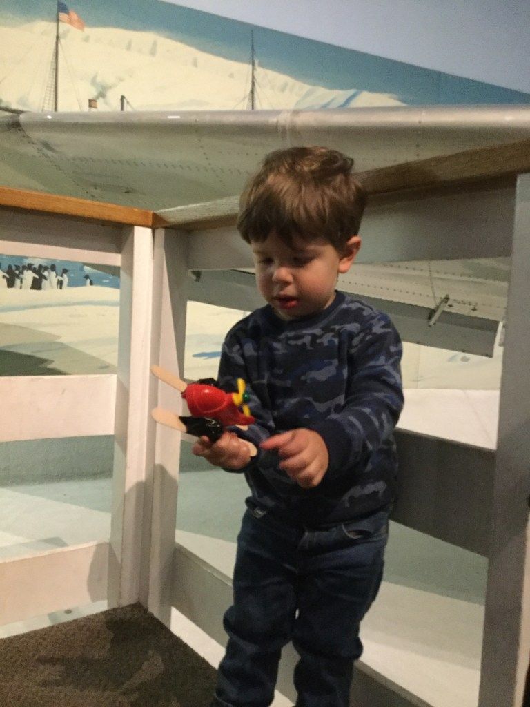 A little boy plays with a toy airplane in front of a real one.