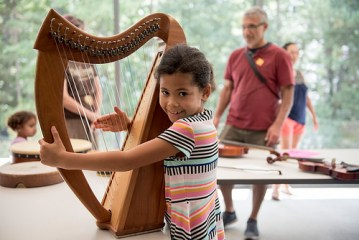 Young girl holding a harp and smiling