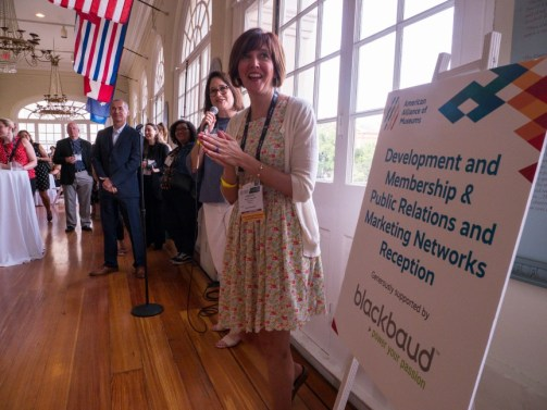 Picture of people standing next to a sign for a sponsored professional network reception. They are smiling and clapping.