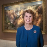 An image of Stephanie Stebich, a woman stands in front of a large landscape artwork wearing a blue top and jacket with short reddish brown hair.