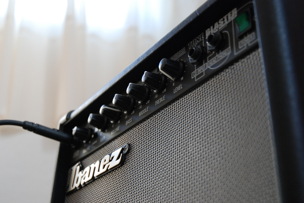 An Ibanez guitar amp with an cord plugged in and lots of dials