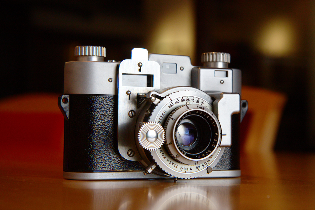 An old camera with mechanical looking lens prominently featured in the image