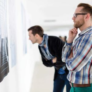 Image of two young white men looking intently at something on the wall.