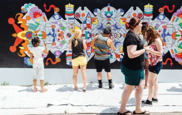 A group of people stand painting an exterior wall with a white woman walking by.