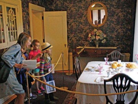 Image of a family of two children viewing the dining room at the Pittock Mansion.