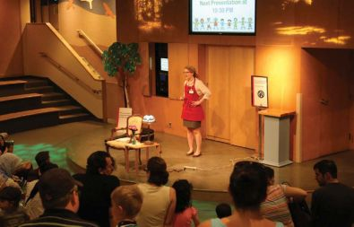 A woman in a red apron stands on a stage in front of a set of doors lecturing an audience of adults and children.