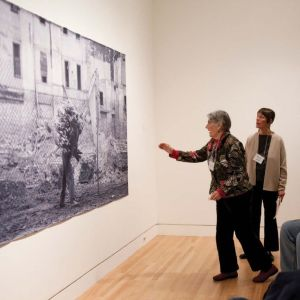 Two women examine a large format photograph on the wall. One of the women is reaching toward the image.