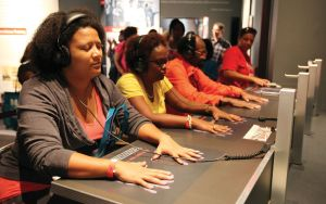 Image of a group of people sitting at a long tabel with their hands on hand prints in front of them each with a set of headphones listening.