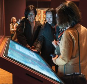 Three women look down on an angled interactive screen.