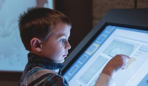 A young white boy touches an interactive screen.