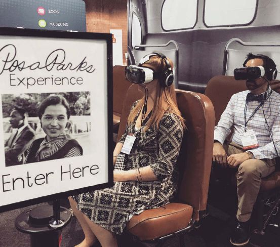 A woman sits in front of a man in a bus like exhibition area wearing VR masks and headphones.