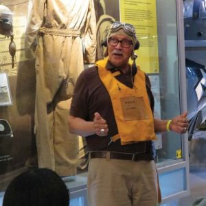 A grey haired man wearing a deflated flotation device stands in front of a museum case and appears to be giving a tour.
