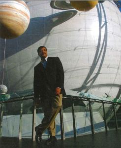 Neil deGrasse Tyson leaning on a metal railing with a few planets behind.