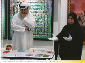 A man wearing a white long shirt and headdress and a woman wearing a black burka stand by a table explaining the right way to handle an object.