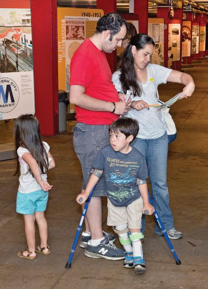 A family stands reading a map in a gallery with two small children, one has leg braces and crutches.