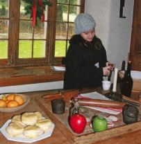 A young teen works with kitchen utensils in a historic kitchen.