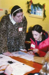 A costumed interpreter looks over a young teen's writing work.