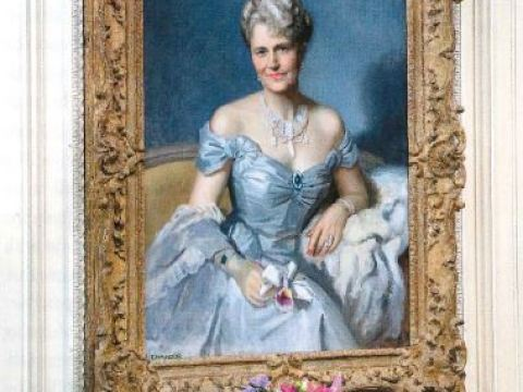 A portrait of a grey haired woman in a white dress hangs above an ornate fireplace.