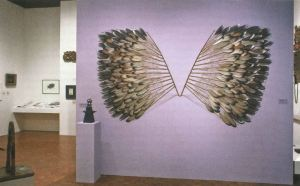 View of an artwork handing on a wall made of feathers looking like wings.